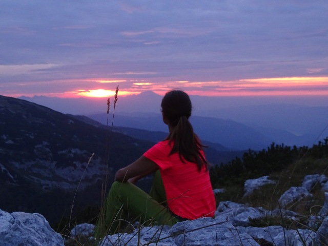 A female hiker expecting sunrise from Mala Tičarica above Triglav lakes, Slovenia