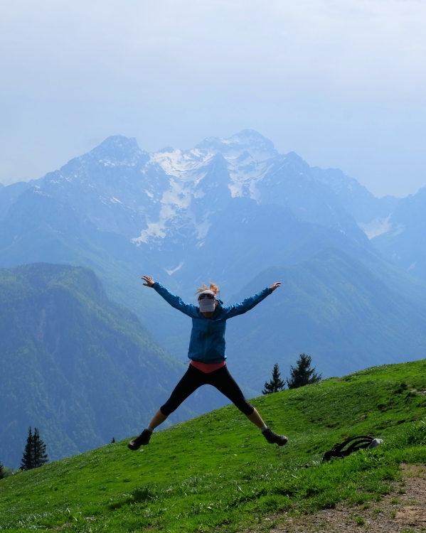 A female hiker jumping from joy in the mountains